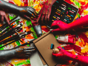 Hands, paint, art in art studio, colorful creative background