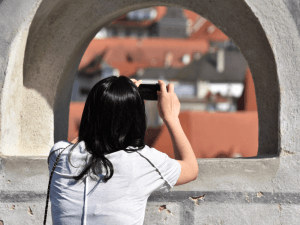 tourism travel girl with a camera on a city street takes a photo