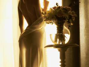 Lifestyle art photo of beautiful sensual blonde with flowers at the window