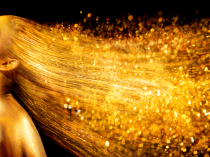 High Fashion model woman in golden bright sparkles