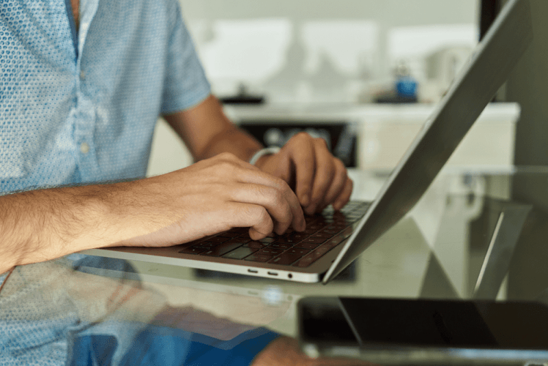 Close up male hands typing on a laptop at home