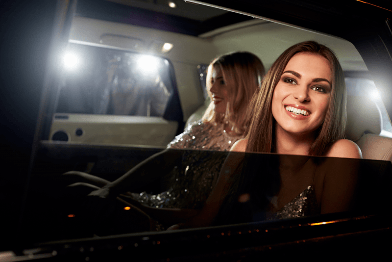 Two women in the back of a limo, photographed by paparazzi