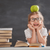 Back to school and happy time! Cute industrious child is sitting at a desk