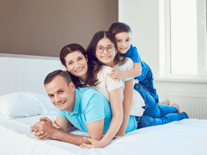Portrait of happy family lying in bedroom