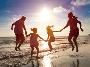 happy family jumping together on the beach